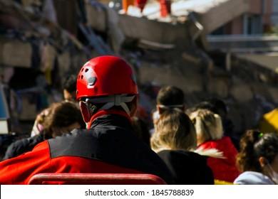 Der Rücken des Such- und Rettungsarbeiters ist vor dem durch das Erdbeben zerstörten Gebäude verschwommen, sah und ruht