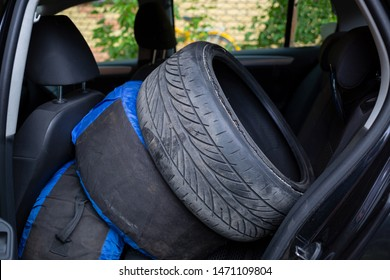 in the back seat of the car are the old destroyed tire and packed  wheels. tire fitting, wheel repair