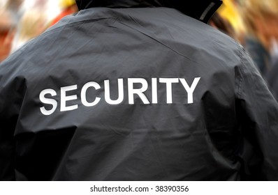 back of a security guard in front of blurred crowd