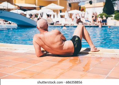 back of senior on the side of swimming pool
