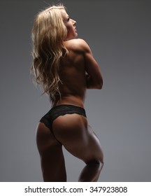 Back of sexy blond woman with soft skin in shadows.