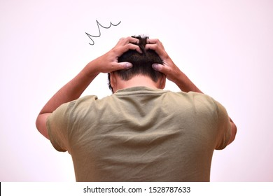 The back of a shocked man holding his head.