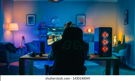 Back Shot of a Gamer Playing First-Person Shooter Online Video Game on His Powerful Personal Computer. Room and PC have Cold Colorful Neon Led Lights. Cozy Evening at Home.