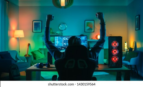 Back Shot of a Gamer Playing and Winning in First-Person Shooter Online Video Game on His Powerful Personal Computer. Room and PC have Green Neon Led Lights. Cozy Evening at Home.