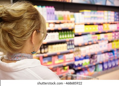 Back shot of grandmother with blonde hair shopping at local supermarket, pushing cart forward going to household chemistry section to buy laundry detergent or shampoo, against blurred background