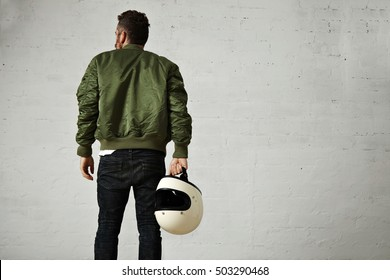 Back shot of a hip bearded pilot in green bomber jacket, skinny jeans and with a white blank helmet in his hand in a studio with white walls
