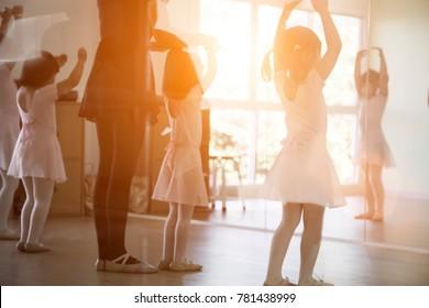 back shot of kid practice ballet dance in studio in morning light