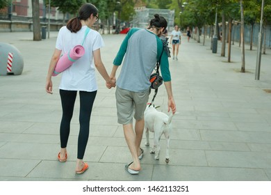 Back shot of a young binary unfocused couple of white man and woman walking his dog moving while holding each others hands on Madrid city street. Coming back home from outdoor yoga activity concept.