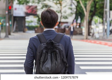 Back shot of young business man with backpack bag during early morning