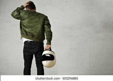 Back shot of a young motorcyclist in jeans, military bomber jacket and holding his white helmet touching his hair isolated on white