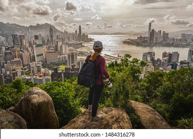 Back side of asia woman photographer standing and shooting after climbing the peak of hong kong mountain and looking hong kong and kowlloon cityscape at sunset time,adventure and travel concept