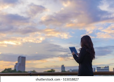 Back side of Asian businesswoman holding digital tablet, reading, touching the screen and sunset sky background. (Concept of technology or communication and leave space for adding your content)