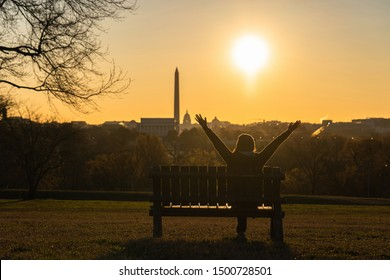 Back side of asian woman sitting and Lifting hands for success over the Washington DC Landmark which can see United states Capitol, washington monument and lincoln memorial at the sunrise time,