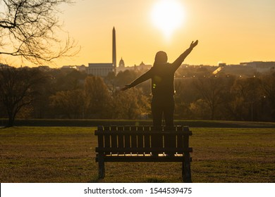 Back side of asian woman standing and Lifting hands for success over the Washington DC Landmark which can see United states Capitol, washington monument and lincoln memorial at the sunrise time,