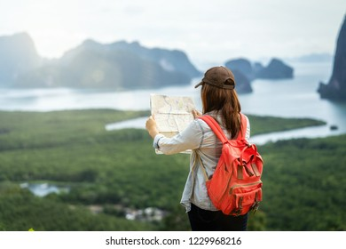 Back side of Asian woman traveler looking the map for travel with backpacker at Fantastic Landscape of samed nang chee view point, travel and holiday concept