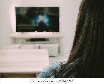 back side of black hair woman sit, relax and watch TV in her living room with soft focus interior object background