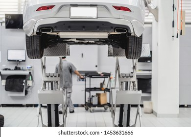 Back side of Car lifted in automobile service and Asian mechanic Checking and torch tire in maintainance service center which is a part of showroom,technician or professional work for customer concept