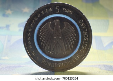 back side of a five euro coin with eagle and blue shining circle