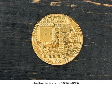 Back side of the gold coin bitcoin on wooden background, top view