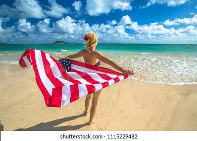 Back side Hawaiian woman holding a waving American flag in American flagged bikini. Tropical Lanikai Beach, east shore of Oahu in Hawaii, USA. Freedom and 4th July patriotic concept.