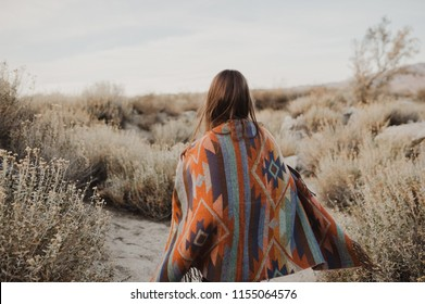 Back side of  hipster traveler girl with windy hair in gypsy look in desert nature.  Artistic photo of young hipster traveler girl in gypsy look, in Coachella Valley in a desert valley in Southern Cal