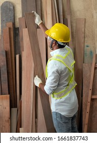 Back side of human wearing glove and yellow helmet,choosing timber board,doing wood work at factory,Handmade design