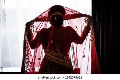 Back side of an Indian / Pakistani Bride wearing Red Dress Lehenga.