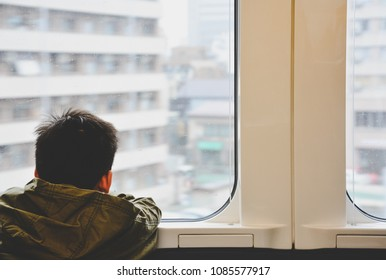 back side of little boy traveling by train and looking out through glass window with cityscape background, copy space, child problem or travel concept, vintage effect