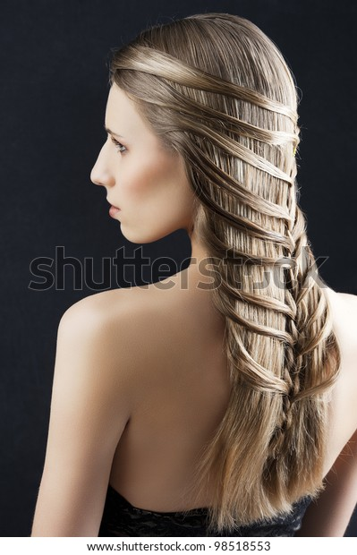back side portrait of a fashion woman with long hair and old style and creative hairstylish, she is turned at her left and looks at left