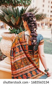 Back side portrait of Indian woman wearing saree and beautiful braided hairdo on her long hair
