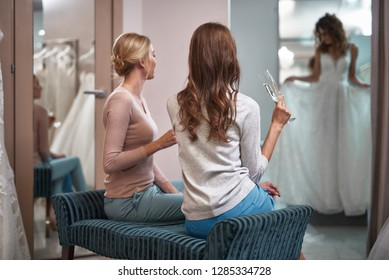 Back side portrait of two young women sitting in wedding salon with champagne and looking at their female friend while she trying on bridal dress