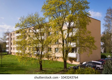 Back side of a residential block of flats apartament house building in a tonw or city, spring trees and green lawn