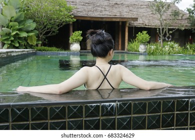 back side of sexy woman enjoy relexing from the pool, travel and tourism concept