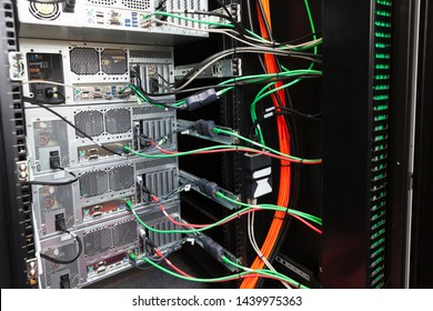 Back side of a small server rack with computer stations, network equipment and data cables