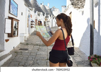 Back side of traveler girl searching right direction on map. Young woman visit Alberobello trulli in Apulia region, Italy