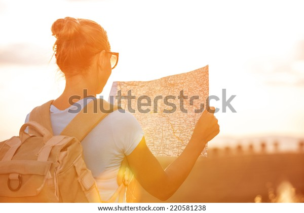 Back side of traveler girl searching right direction on map, bright orange sunset light, traveling along Europe, freedom and active lifestyle concept