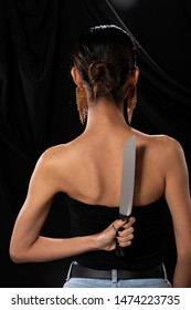 Back side view of Asian Woman wrapped hair hold Kitchen sharp Knife in hand, studio lighting black backgrounds, ready to betray by stabbing