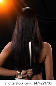 Back side view of Asian Woman long hair hold Kitchen sharp Knife in hand, studio lighting black backgrounds, ready to betray by stabbing