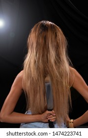 Back side view of Asian Woman long dyed blonde hair hold Kitchen sharp Knife in hand, studio lighting black backgrounds, ready to betray by stabbing