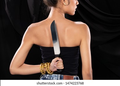 Back side view of Asian Woman wraped hair hold Kitchen sharp Knife in hand, studio lighting black backgrounds, ready to betray by stabbing