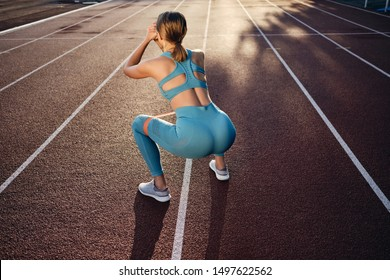 Back side view of athlete girl in stylish sportswear squatting with rubber band during workout on city stadium
