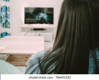 back side view of black hair woman sit, relax and watch TV in her living room with soft focus interior object background