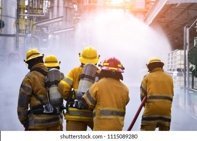 The Back side view of a group of firefighters helped stop the fire. Fire in the Industrial Factory . Rescue ,Teamwork concept .