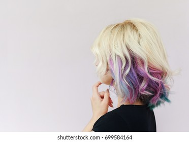 Back or side view of imagined woman with colorful hair looking at white wall with space for text. Business woman making a plan.