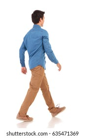 back side view of a walking young casual man on white background