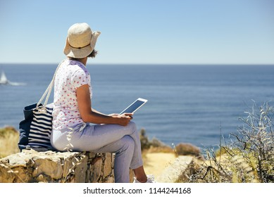 Back side view of woman sitting holding tablet computer, ocean sunny natural background. Traveler having fun international travelling lifestyle, phone technology social communication, amazing nature