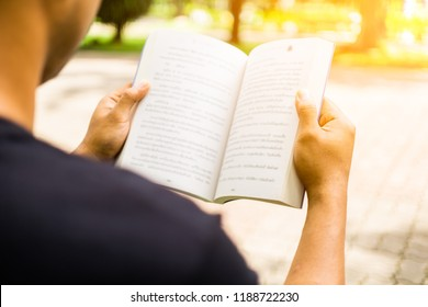 Back side view young asian man opening book and reading book in park. Relax time concept.