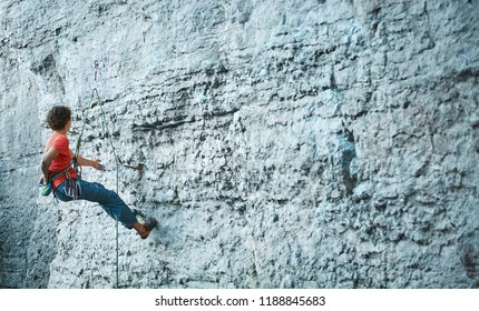 back side view of young man rock climber in bright blue pants climbing on the cliff. rock climber climbs on a rocky wall. man making hard move on the challenging route