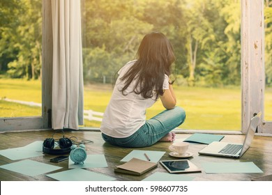Back side of woman with frustrated, overworked at home and near the girl is alarm clock, book, tablet, laptop and background blur beautiful garden at home. (vintage color tone, lens blur effect)
