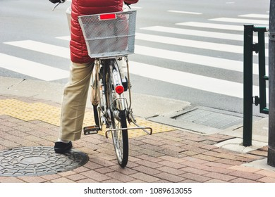 back side of woman on vintage bicycle waiting at the sidewalk for cross the road at the crosswalk, urban lifestyle concept